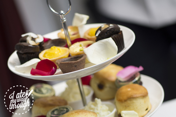 High tea service with chocolate tarts, lemon tarts, cupcakes and scones