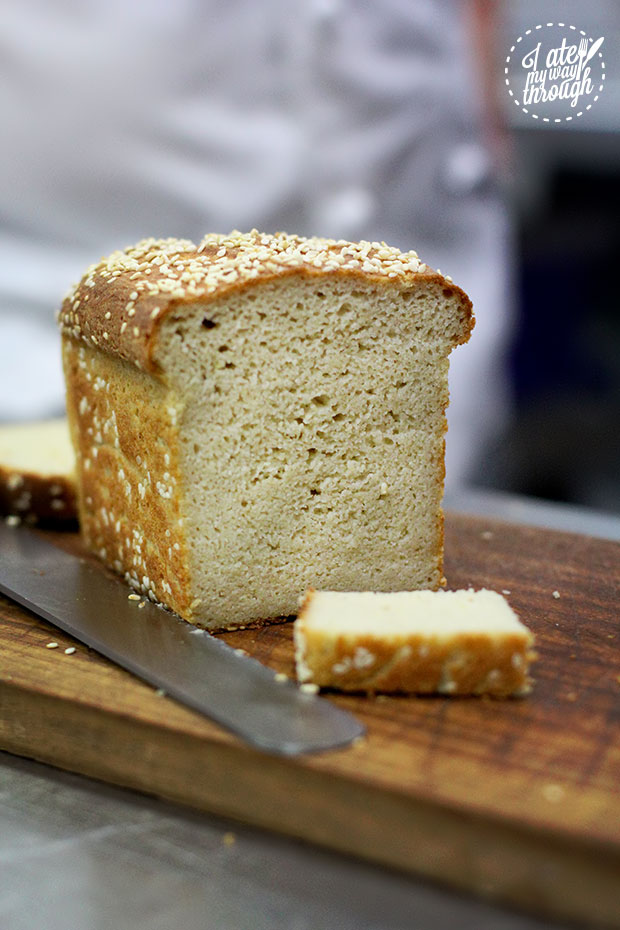 A gluten free bread loaf, sitting on a wooden board, with a slice cut off.