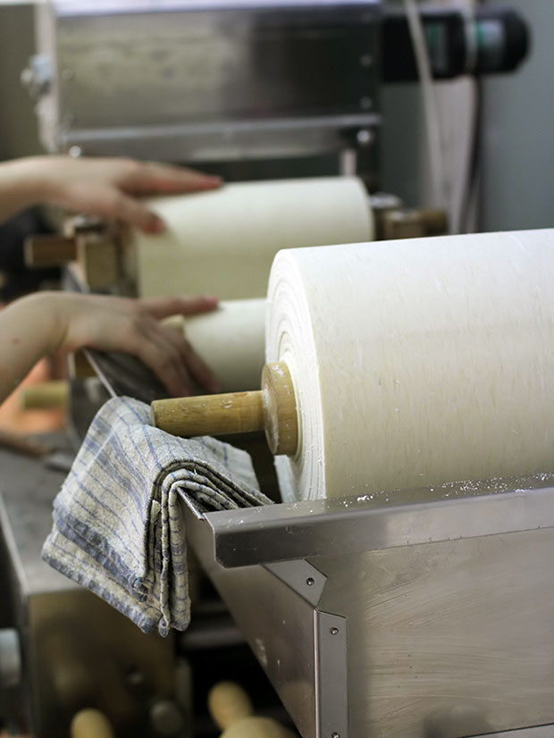 Sheets of wheat dough are being rolled through various rollers, resulting in consistently perfect ramen each time.