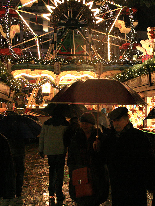 Christmas markets in Germany. Crowds gather under bright lights and frosty conditions.