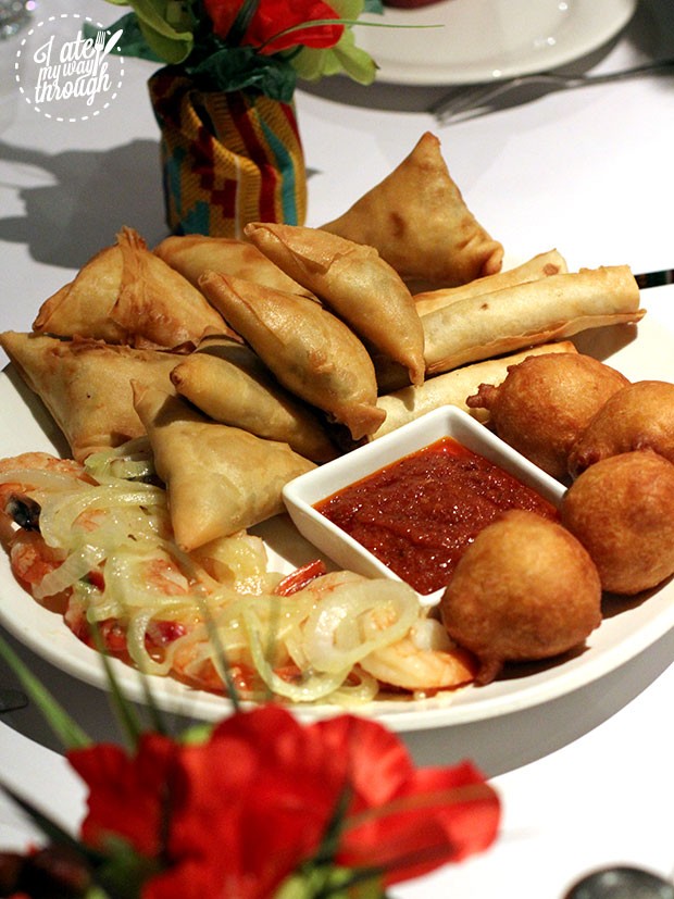 African entree platter, with samosas, dumplings, mince cigars, and a red dipping sauce.