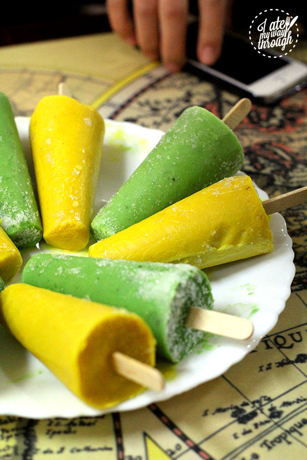 Pistachio and mango popsicles, coloured green and yellow, and placed alternately on a white plate.