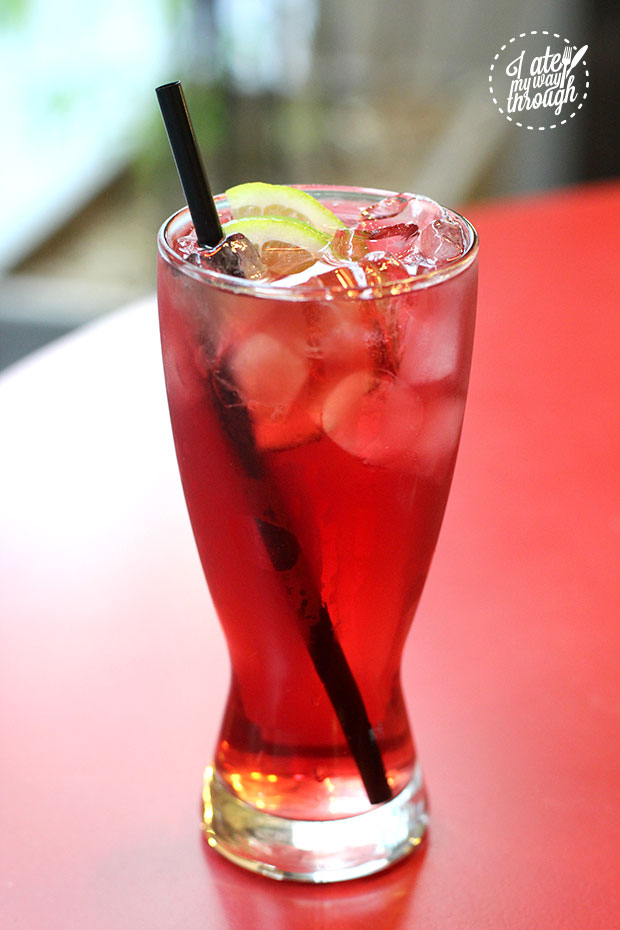 Raspberry and lime iced tea, in a tall glass.