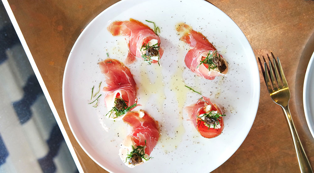 Jamon, Watermelon and Persian Feta bites, arranged in a circle on a white plate.