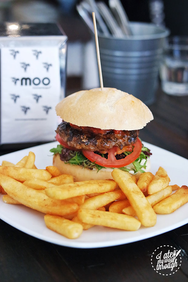 A classic burger sits behind golden brown chips, part of Moo Gourmet Burger's student meal deals