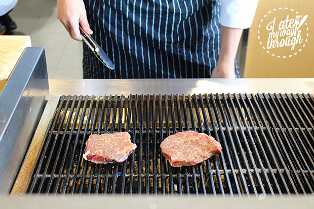Meat being cooked by a chef on the grill