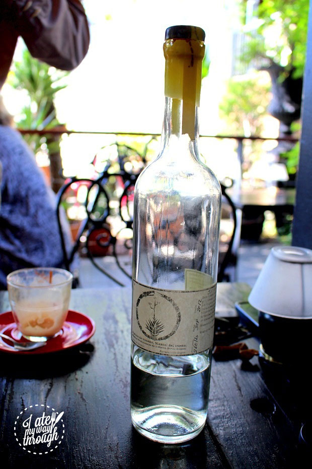 A clear bottle of Mezcal showcases a clear, dense liquid