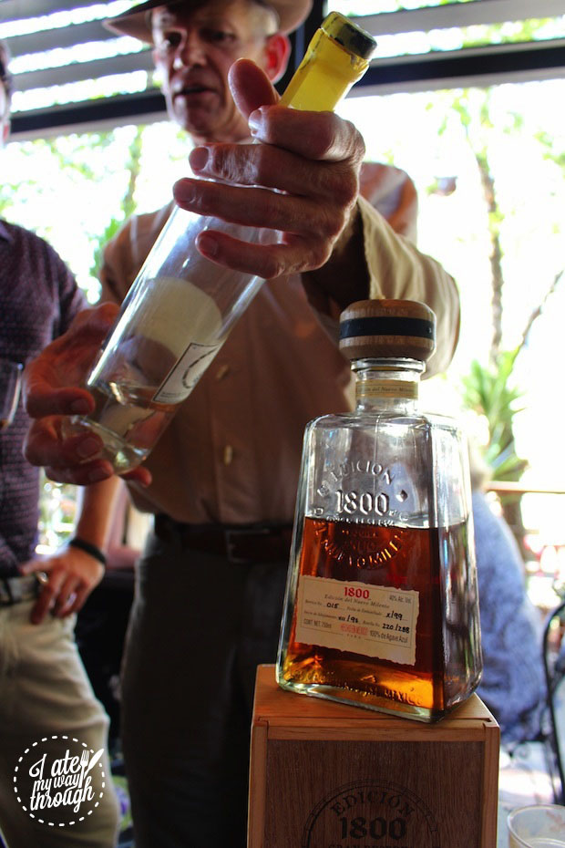 Phillip Bayly showcasing a bottle of mezcal