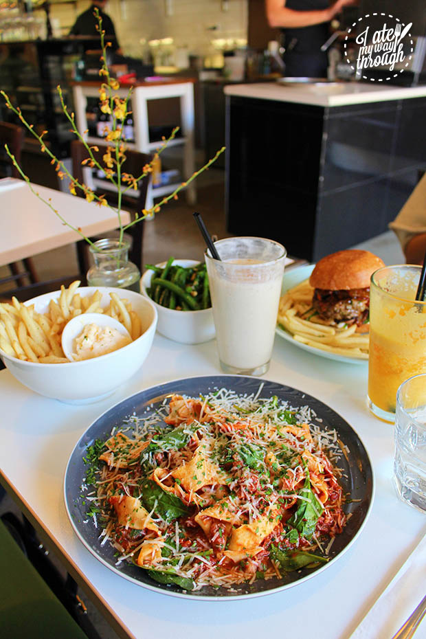 Pasta, beverages, sides and burger on table