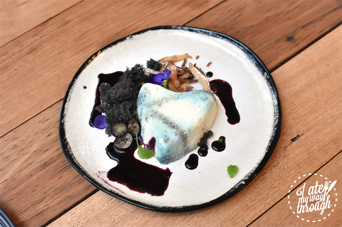 The finished couer a la crème dessert with blueberry, black sesame sponge and lemon balm