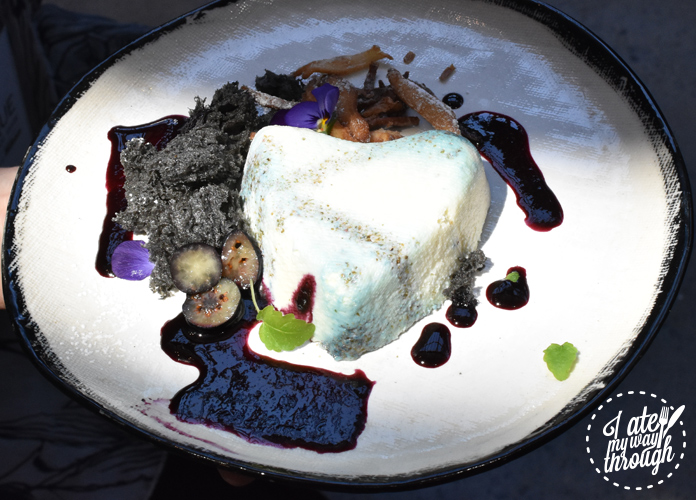The finished couer a la crème dessert with blueberry, black sesame sponge and lemon balm pictured in a natural spotlight. Created by BlackStar Pastry's Christopher Thé
