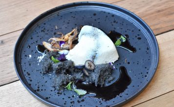 The finished couer a la crème dessert with blueberry, black sesame sponge and lemon balm pictured on a black plate. Created by BlackStar Pastry's Christopher Thé