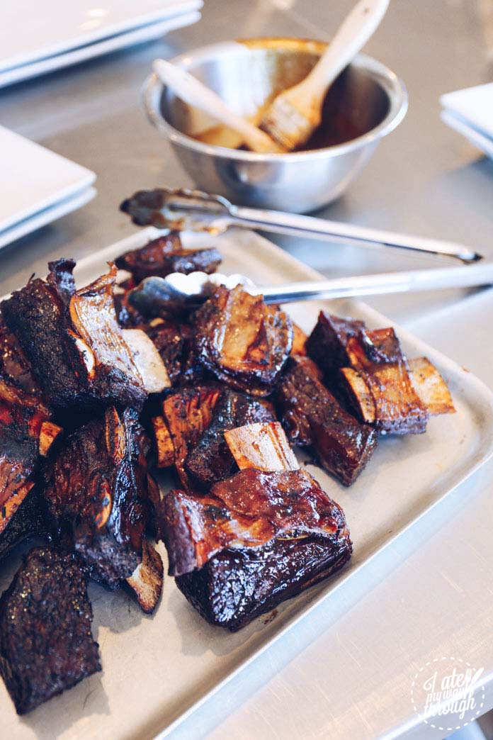 Twice cooked sticky soy glazed beef ribs ready to be served with cucumber and pickled garlic salad